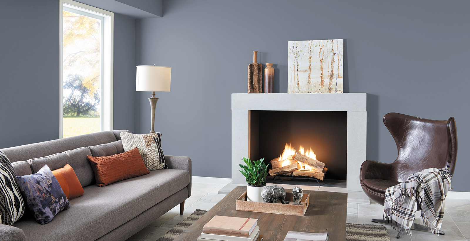 Casual styled living room with grayish blue on walls, white on trim, light gray couch and wood coffee table