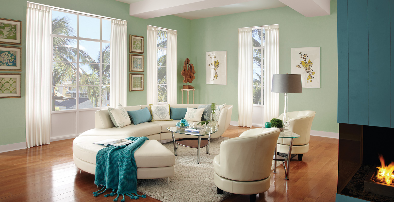 Coastal living room with pale green on main walls, teal on wall with fireplace, white on trim, and cream couch and chairs