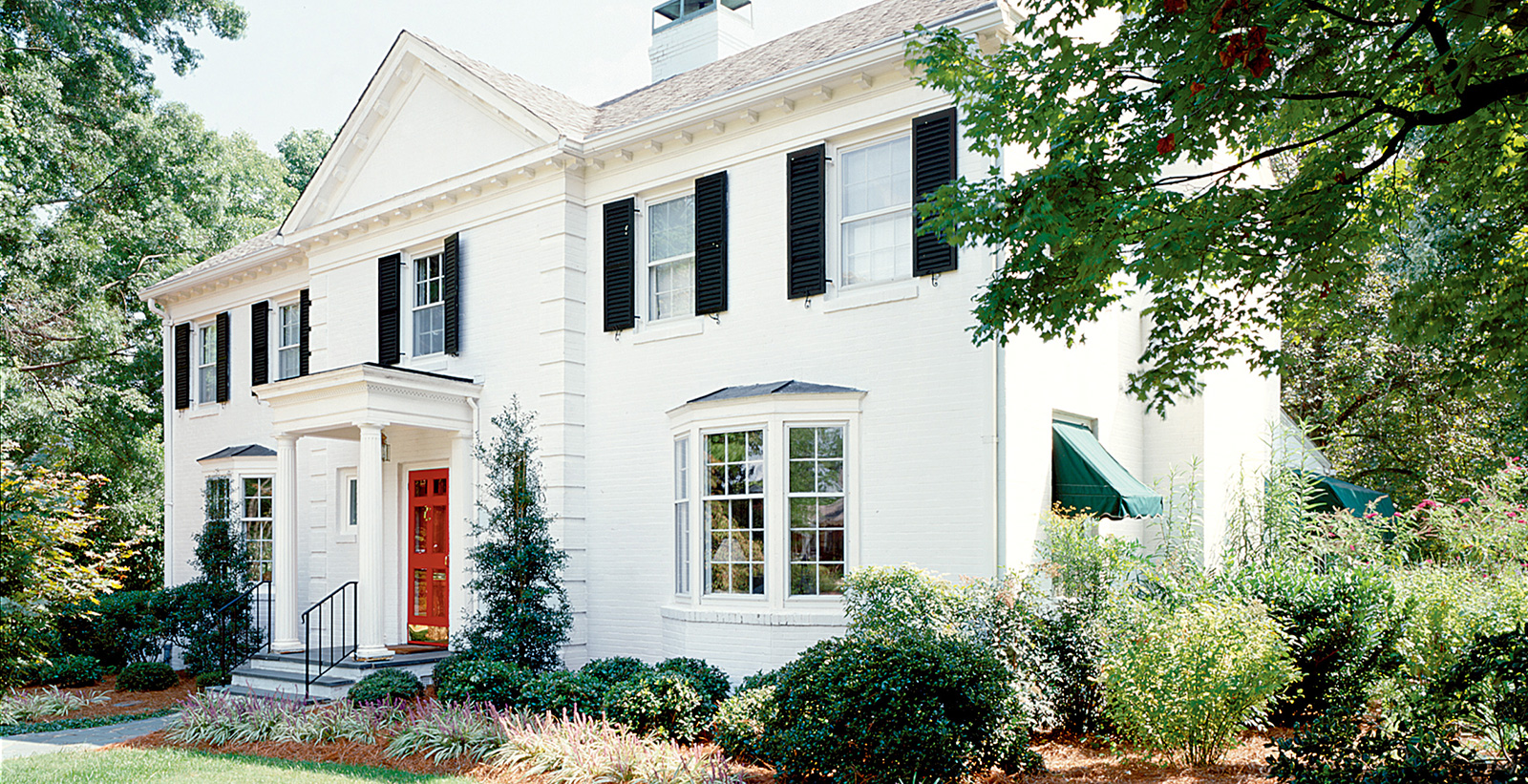 Colonial themed house with white walls, white trim, black shutters, and red door.