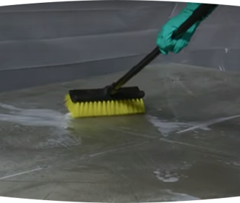 Person scrubbing the floor with a large brush