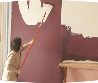 A person painting a wall with extension roller