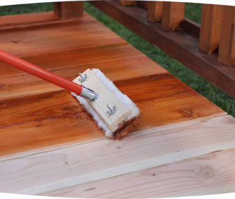 A brush applying stain to a deck